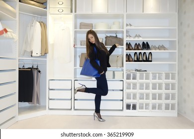 Young and beautiful woman with fashion bag undecided on a pair of high heels shoes to wear inside a walk-in closet. Elegant girl tries a pair of shoes before a purchase in a clothes store.