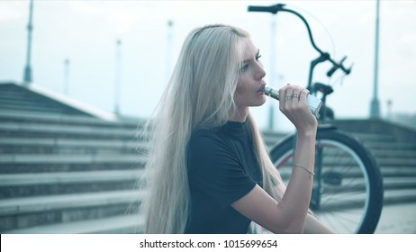 Young beautiful woman with fashion makeup at the bar with a with vapor from electronic cigarette