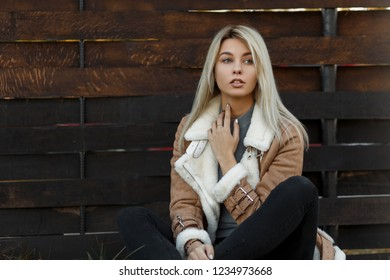 Young beautiful woman in a fashion season beige jacket with a fur collar and gray sweater sits on grass near a wooden fence. Trendy modern lookbook. Attractive girl