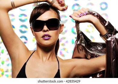 Young beautiful woman with fashion sunglasses holding handbag