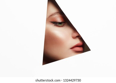 young beautiful woman. female face with makeup into paper hole. make-up artist concept. arrows on the eyes.