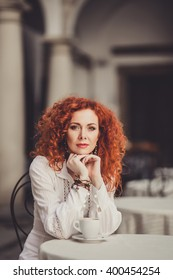 young beautiful woman with fiery red curly hair, sitting in a vintage retro cafe restaurant and coffee morning drink tasty cappuccino, nice table, outdoor portrait, close up, italy venecia