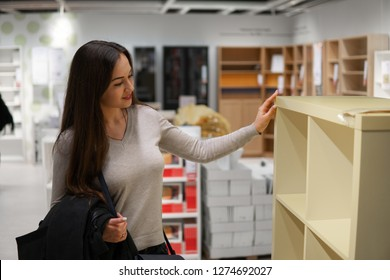 young beautiful woman finding herself new furniture, decoration warehouse goods in a store supermarket shop.