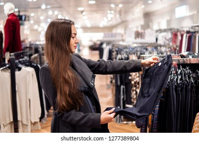 young beautiful woman finding herself new clothes in a store supermarket shop