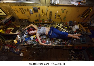 A young beautiful woman finds time to sleep during  her working hours. She lies down on the work bench filled with tools and other electronic devices.