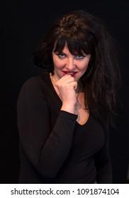 Young beautiful woman flirts on black background