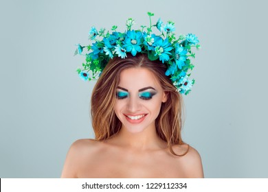 Young beautiful woman with floral crown on head smiling happy looking down posing on light green blue studio background with copy space. Multicultural model with headband from flowers