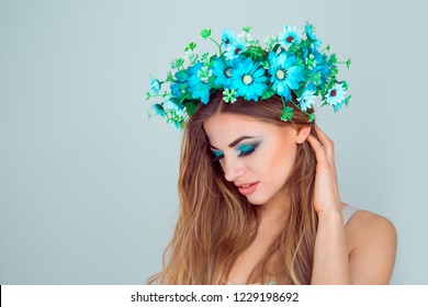 Young beautiful woman with floral crown on head in side profile looking down posing on light green blue studio background with copy space Multicultural beauty model with headband from anemone flowers