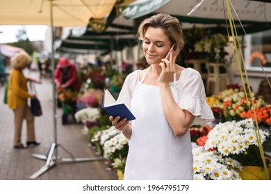 Young and beautiful woman florist taking order by phone in her little flower shop