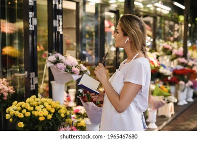 Young and beautiful woman florist taking new order by phone using wireless earbuds in her little flower shop
