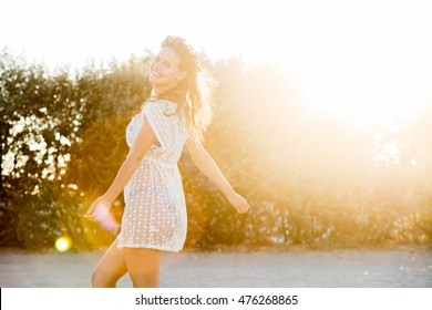 young beautiful woman with flower crown and summer dress walking and dancing on a beach at sunset with smile and joy