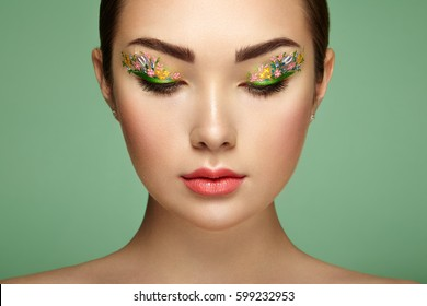 Young beautiful woman with flower makeup eyes. Spring makeup. Beauty fashion. Eyelashes. Cosmetic Eyeshadow. Make-up detail. Girl on green background