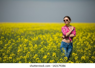 Young beautiful woman in flowering field in summer. Outdoors