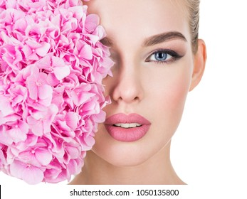 Young beautiful woman with flowers near face. Pretty female with health, fresh skin of body. Lady with pink makeup of eyes.