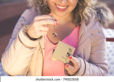 Young beautiful woman get a heart shape gold necklace gift from her boyfriend on Valentines Day. Closeup view.