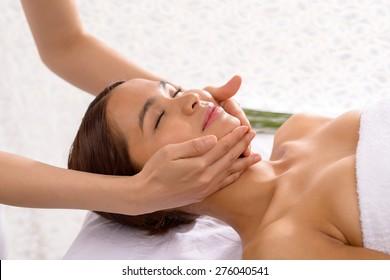 Young beautiful woman getting facial massage at spa resort