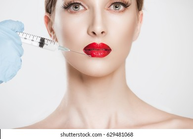 Young beautiful woman getting ready for lips augmentation, plastic surgery, doctor's hand in blue gloves holding injection near her lips isolated white background.