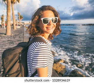 young beautiful woman girl with a backpack walks along the seashore and embankment in the city at sunset, travel and vacation concept, happiness, joy and freedom