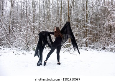 Young beautiful woman girl in black ballet suit presents herself with a black cloth in snowy winter forest