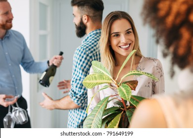 Young beautiful woman giving present to her friend. Friends meeting for moving into a new house.