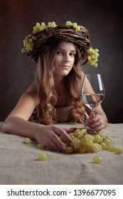 Young beautiful woman with glass of white wine. Vine wreath with grapes on a head. Beautiful girl with long wavy hair and perfect make-up.