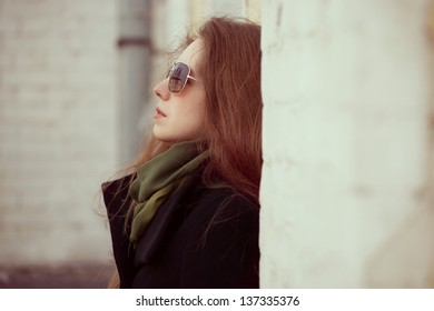 Young beautiful woman with glasses against the wall at home