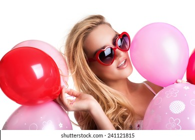 Young beautiful woman with glasses holding red pink balloons, valentine's day