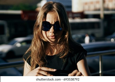 Young beautiful woman with glasses on the street in the city.