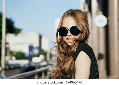 Young beautiful woman with glasses on the street in the evening.