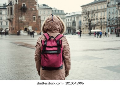 Young beautiful woman with glasses stands in the middle of the main square of Krakow with textile backpack