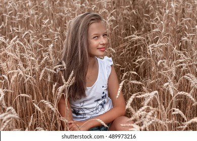 Young beautiful woman in golden wheat field. Adorable little girl playing in the wheat field on a warm summer day.