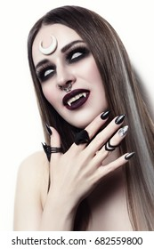 Young beautiful woman with gothic Halloween make-up and fangs