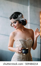 Young beautiful woman is gracefully holding a Cup in one hand.Elegant hairstyle on dark hair. Exclusive dress, decoration on head in retro style.Fantastic shooting.Fashionable toning.Creative color.