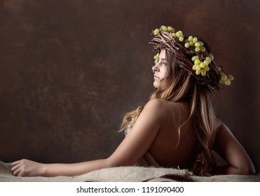 Young beautiful woman with grapes. Vine wreath with grapes on a head. Beautiful girl with long wavy hair and perfect make-up.