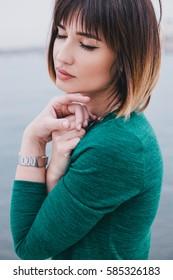 Young beautiful woman in a green dress near sea