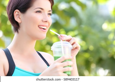 Young beautiful woman with green smoothie outdoor