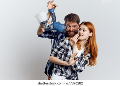 Young beautiful woman and guy with beard on white isolated background, repair, building materials, tools.