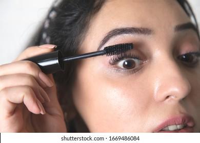 young beautiful woman hand Mascara on brick wall background