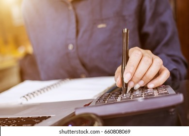 Young beautiful woman hand using pen point to calculator with notebook and laptop at office in the morning.