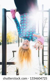 Young beautiful woman hanging upside down on horizontal bar at calisthenics park, looking at the camera giving high five