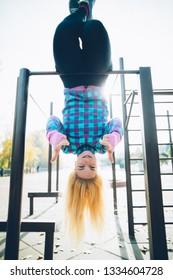 Young beautiful woman hanging upside down on horizontal bar at calisthenics park, looking at the camera giving thumbs up