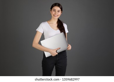 Young beautiful woman has happy facial expression, holds laptop, smiling, looking at the camer, wearing white t-shirt, isolated on grey background