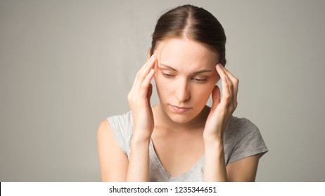 Young beautiful woman has headache, isolated