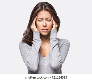 Young beautiful woman has headache, isolated on gray background