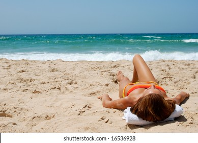Young beautiful woman has a rest on coast of ocean