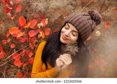 Young beautiful woman in hat in the autumn forest