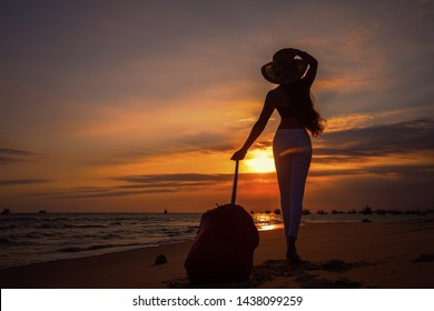Young beautiful woman in  hat with large suitcase on tropical beach at sunset