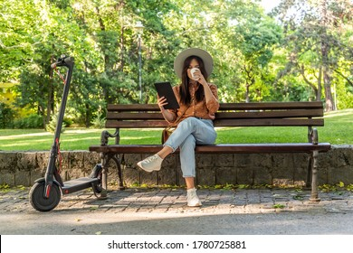 A young beautiful woman with a hat is sitting on a park bench with the tablet in her hands while drinking coffee. An electric scooter is parked next to her, while trees predominate in the background.
