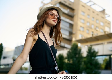 Young beautiful woman in a hat and sunglasses walking around the city on the street.