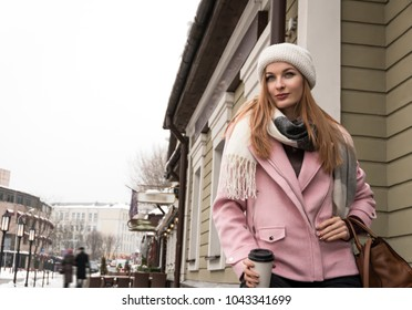 Young beautiful woman in a hat walking around the city